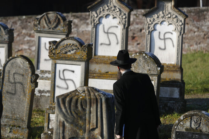 FILE - In this Dec. 4, 2019 file photo, Strasbourg chief Rabbi Harold Abraham Weill looks at vandalized tombs in the Jewish cemetery of Westhoffen, west of the city of Strasbourg, eastern France. Coronavirus lockdowns in 2020 shifted some anti-Semitic hatred online, where conspiracy theories blaming Jews for the pandemic's medical and economic devastation abounded, Israeli researchers at Tel Aviv University's Kantor Center for the Study of Contemporary European Jewry in an annual report Wednesday, April 7, 2021. (AP Photo/Jean-Francois Badias, File)