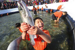 A boy shouts after catching a trout during a contest in Hwacheon, South Korea, on Saturday, Jan. 6, 2018. The contest is part of an annual ice festival which draws over 1,000,000 visitors every year. (AP Photo/Ahn Young-joon)