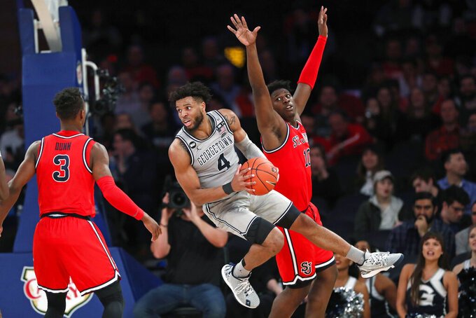 Georgetown guard Jagan Mosely (4) leaps to pass with St. John's forward Marcellus Earlington (10) defending and St. John's guard Rasheem Dunn (3) watching during the second half of an NCAA college basketball game in the first round of the Big East men's tournament Wednesday, March 11, 2020, in New York. (AP Photo/Kathy Willens)