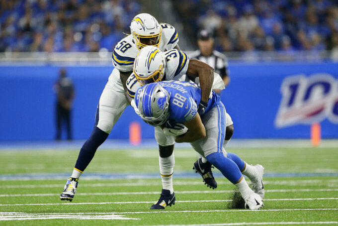 Detroit Lions tight end T.J. Hockenson (88) is brought down by Los Angeles Chargers defensive back Adrian Phillips (31) and Thomas Davis (58) in the first half of an NFL football game in Detroit, Sunday, Sept. 15, 2019. (AP Photo/Duane Burleson)