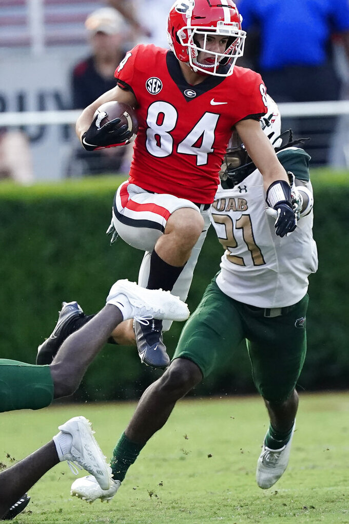 Georgia wide receiver Ladd McConkey (84) leaps over the pile as he tries to escape from UAB safety Will Boler (21) after a catch during the second half of an NCAA college football game Saturday, Sept. 11, 2021, in Athens, Ga. (AP Photo/John Bazemore)