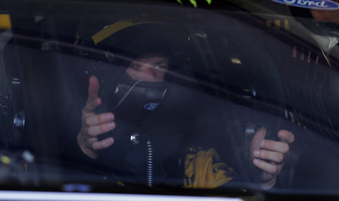 Pole sitter Brad Keselowski mounts the steering wheel on his car as he prepares to head to the track during a NASCAR Cup Series auto race practice at New Hampshire Motor Speedway in Loudon, N.H., Saturday, July 20, 2019. (AP Photo/Charles Krupa)