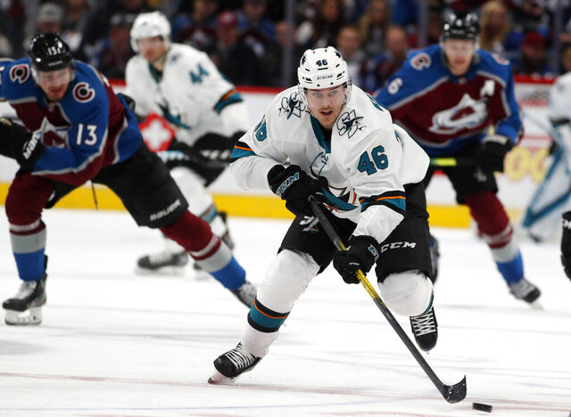 San Jose Sharks center Joel Kellman, front, drives down the ice with the puck with Colorado Avalanche right wing Valeri Nichushkin, back left, and defenseman Erik Johnson in pursuit during the second period of an NHL hockey game Thursday, Jan. 16, 2020, in Denver. (AP Photo/David Zalubowski)