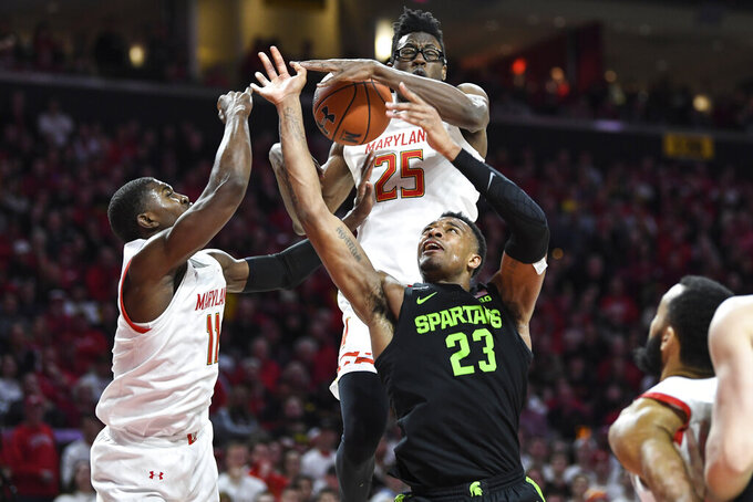 Michigan State forward Xavier Tillman Sr. (23) has his shot blocked by Maryland forward Jalen Smith (25) during the first half of an NCAA college basketball game Saturday, Feb. 29, 2020, in College Park, Md. (AP Photo/Terrance Williams)