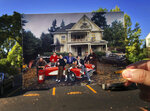 In this July 27, 2018 photo, a photograph from the movie  Animal House is held upat the site where the fictitious Delta Tau Chi fraternity was featured in Eugene, Ore.  Forty years later, the signature location is long gone, replaced by a parking lot. The dilapidated Eugene home on East 11th Avenue that was the namesake for the movie