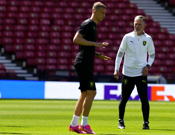 Czech Republic's manager Jaroslav Silhavy, right, watches as Czech Republic's Tomas Soucek warms up during a training session at the Hampden Park Stadium in Glasgow, Sunday, June 13, 2021, the day before their first match against Scotland. (AP Photo/Petr David Josek,)