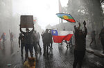 Anti-government demonstrators are sprayed by a police water cannon during a protest in Santiago, Chile, Saturday, Oct. 26, 2019. Chile has been facing days of unrest, triggered by a relatively minor increase in subway fares. The protests have shaken a nation noted for economic stability over the past decades, which has seen steadily declining poverty despite persistent high rates of inequality. (AP Photo/Rodrigo Abd)