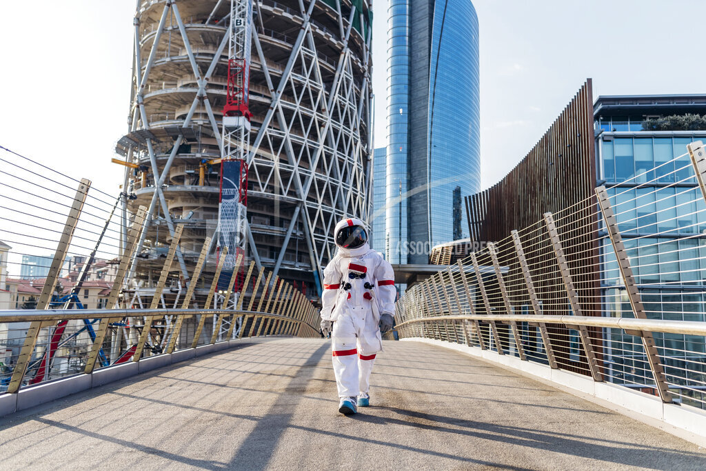 Mid adult astronaut wearing space suit walking on bridge during sunny day