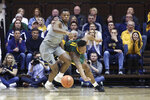 West Virginia forward Oscar Tshiebwe (34) and Baylor guard Mark Vital (11) go for a loose ball during the second half of an NCAA college basketball game Saturday, March 7, 2020, in Morgantown, W.Va. (AP Photo/Kathleen Batten)