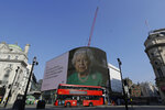 An image of Britain's Queen Elizabeth II and quotes from her historic television broadcast commenting on the coronavirus pandemic are displayed on a big screen at Piccadilly Circus in London, Thursday, April 9, 2020. British Prime Minister Boris Johnson remains in intensive care with the coronavirus but is improving and sitting up in bed, a senior government minister said Wednesday, as the U.K. recorded its biggest spike in COVID-19 deaths to date. The new coronavirus causes mild or moderate symptoms for most people, but for some, especially older adults and people with existing health problems, it can cause more severe illness or death. (AP Photo/Kirsty Wigglesworth)