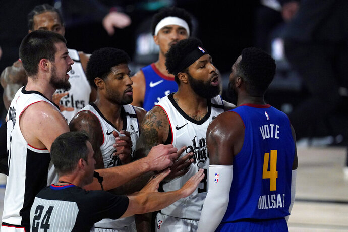 Los Angeles Clippers' Marcus Morris Sr., second from right, and Denver Nuggets' Paul Millsap scuffle during the first half of an NBA conference semifinal playoff basketball game, Friday, Sept. 11, 2020, in Lake Buena Vista, Fla. (AP Photo/Mark J. Terrill)