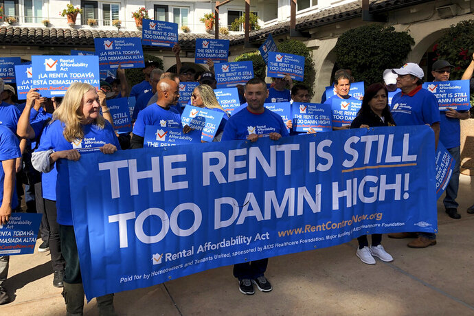 Supporters of the Rental Affordability Act hold up signs during a news conference Thursday, Dec. 5, 2019, in Los Angeles. (AP Photo/Michael Blood)