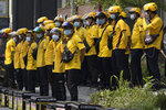 Delivery men wearing masks to curb the spread of the coronavirus gather for a briefing before work in Beijing Thursday, July 23, 2020. (AP Photo/Ng Han Guan)