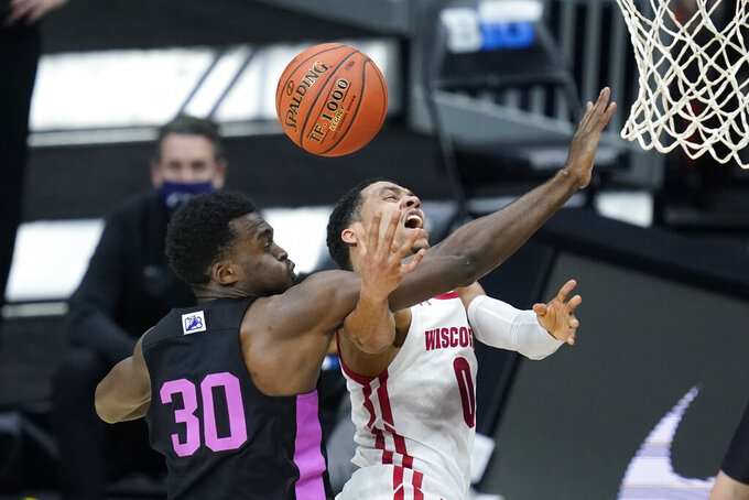 Wisconsin's D'Mitrik Trice (0) is fouled by Penn State's Abdou Tsimbila (30) as he goes up for a shot during the first half of an NCAA college basketball game at the Big Ten Conference tournament, Thursday, March 11, 2021, in Indianapolis. (AP Photo/Darron Cummings)