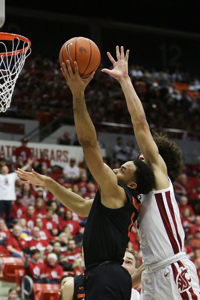 Oregon State guard Sean Miller-Moore, left, shoots in front of Washington State forward CJ Elleby during the second half of an NCAA college basketball game in Pullman, Wash., Saturday, Jan. 18, 2020. Washington State won 89-76. (AP Photo/Young Kwak)