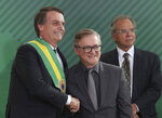In this Jan. 1, 2019 photo, Brazil's President Jair Bolsonaro, left, shakes hands with Education Minister Ricardo Velez Rodriguez, during a swearing-in ceremony for his cabinet at the Planalto presidential palace, in Brasilia, Brazil. Velez Rodriguez vowed in his inaugural speech to end the