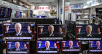 A man stands near TV screens showing a news program reporting about U.S. President Joe Biden's inauguration, at an electronic shop in Seoul, South Korea, Thursday, Jan. 21, 2021. (AP Photo/Lee Jin-man)