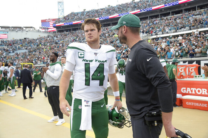 FILE - In this Oct. 27, 2019, file photo, New York Jets head coach Adam Gase, right, talks to quarterback Sam Darnold (14) on the sideline prior to the start the first half of an NFL football game against the Jacksonville Jaguars, in Jacksonville, Fla. The Jets are enduring a tough season under first-year coach Adam Gase and young quarterback Sam Darnold they hope will be the foundation of long-term success. (AP Photo/Phelan M. Ebenhack, File)