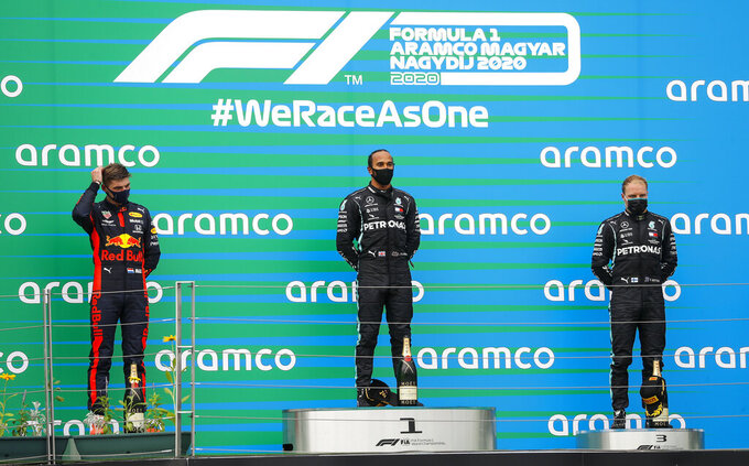 Winner Mercedes driver Lewis Hamilton of Britain, center, stands beside second placed Red Bull driver Max Verstappen of the Netherlands, left, and third placed Mercedes driver Valtteri Bottas of Finland, right, on the podium after the Hungarian Formula One Grand Prix race at the Hungaroring racetrack in Mogyorod, Hungary, Sunday, July 19, 2020. (Leonhard Foeger/Pool via AP)