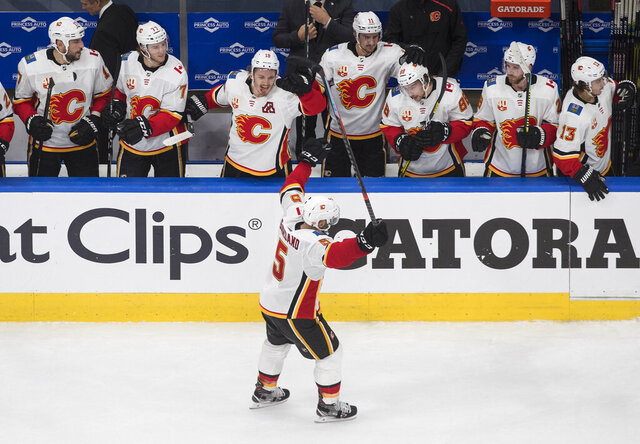 Calgary Flames' Mark Giordano (5) celebrates an empty-net goal with teammates against the Winnipeg Jets during the third period of an NHL qualifying round game, in Edmonton, Alberta, Thursday, Aug. 6, 2020. (Jason Franson=/The Canadian Press via AP)