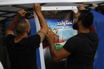In this Thursday, Nov. 7, 2019, Shiite anti-government protesters install an Arabic placard that reads,