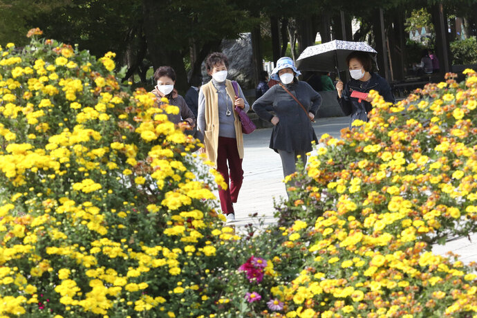 Women wearing face mask to help protect against the spread of the coronavirus pass by flowers at a park in Goyang, South Korea, Thursday, Oct. 15, 2020. South Korea reported on Thursday more than 100 new cases of the coronavirus, half of them linked to a hospital in Busan. (AP Photo/Ahn Young-joon)