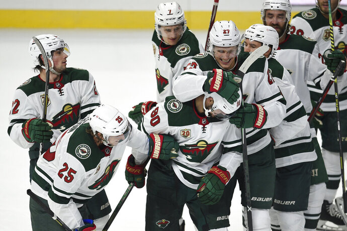 Minnesota Wild players congratulate Marcus Johansson, front center, on his overtime goal in an NHL hockey game against the Los Angeles Kings in Los Angeles, Saturday, Jan. 16, 2021. (AP Photo/Kelvin Kuo)