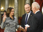 FILE - In this Tuesday, Jan. 3, 2017 file photo, Vice President Joe Biden administers the Senate oath of office to Sen. Kamala Harris, D-Calif., as her husband, Douglas Emhoff, holds the Bible during a a mock swearing in ceremony in the Old Senate Chamber on Capitol Hill in Washington as the 115th Congress begins. President-elect Biden and Vice President-elect Harris are set to take their oaths of office on Wednesday, Jan., 20, 2021, using Bibles that are laden with personal meaning, writing new chapters in a long-running American tradition – and one that appears nowhere in the law.  (AP Photo/Kevin Wolf)