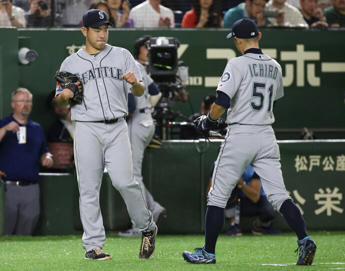 Seattle Mariners starter Yusei Kikuchi, left, welcomes right fielder Ichiro Suzuki after the fourth inning of Game 2 of their Major League baseball opening series against the Oakland Athletics at Tokyo Dome in Tokyo, Thursday, March 21, 2019. (AP Photo/Koji Sasahara)