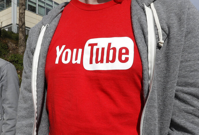 FILE - This April 4, 2018, file photo shows a YouTube logo on a t-shirt worn by a person near a YouTube office building in San Bruno, Calif. YouTube is taking another step to curb hateful and violent speech on its site. The video streaming company said it will now take down videos that lob insults at people based on race, gender expression or sexual orientation. (AP Photo/Jeff Chiu, File)