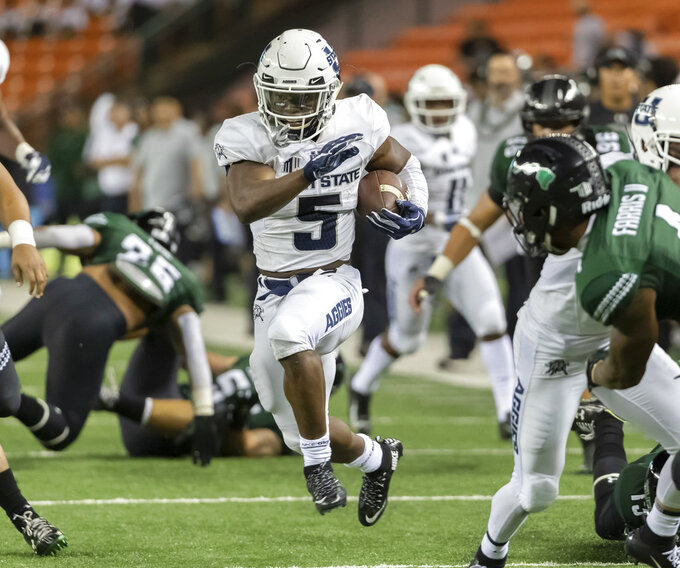 Utah State running back Darwin Thompson (5) shoots through an opening in the Hawaii defense and runs in for a touchdown in the second half of an NCAA college football game, Saturday, Nov. 3, 2018, in Honolulu. (AP Photo/Eugene Tanner)