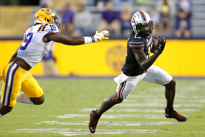 South Carolina wide receiver Shi Smith (13) runs the ball as LSU linebacker Jabril Cox (19) defends during the first half of an NCAA college football game in Baton Rouge, La. Saturday, Oct. 24, 2020. (AP Photo/Brett Duke)