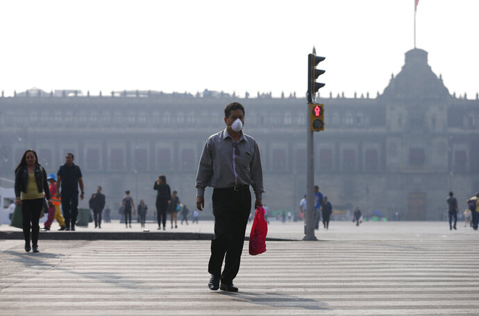 A man wearing a face mask crosses a street backdropped by the National Palace shrouded by haze, in the Zocalo, Mexico City's main square, Thursday, May 16, 2019. A siege of air pollution blanketing the capital has led to school closures and the cancellation of professional sporting events. (AP Photo/Rebecca Blackwell)