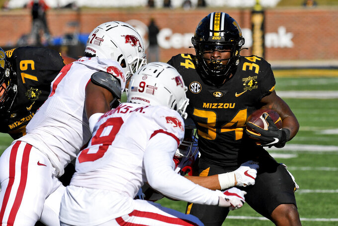 Missouri running back Larry Rountree III (34) runs with the ball as Arkansas defensive back Joe Foucha (7) and defensive back Greg Brooks Jr. (9) defend during the first half of an NCAA college football game Saturday, Dec. 5, 2020, in Columbia, Mo. (AP Photo/L.G. Patterson)