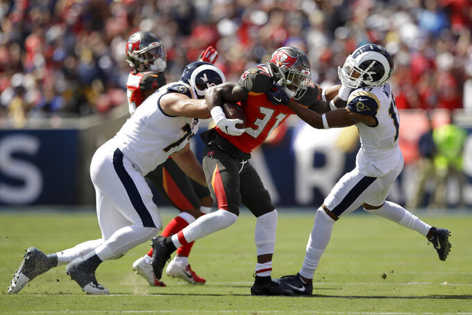 Tampa Bay Buccaneers free safety Jordan Whitehead, middle, is tackled by Los Angeles Rams offensive tackle Andrew Whitworth, left. And wide receiver Robert Woods after an interception during the first of an NFL football game Sunday, Sept. 29, 2019, in Los Angeles. (AP Photo/Marcio Jose Sanchez)