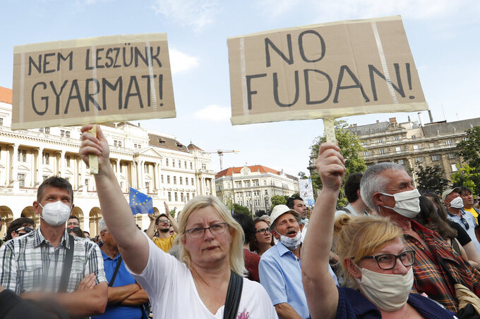 Protesters hold placards reading in Hungarian 'we will not be a colony', left, and 'no Fudan' as they gather in downtown Budapest, Hungary, Saturday, June 5, 2021. Thousands of people gathered opposing the Hungarian government's plan of building a campus for China's Fudan University in Budapest. (AP Photo/Laszlo Balogh)