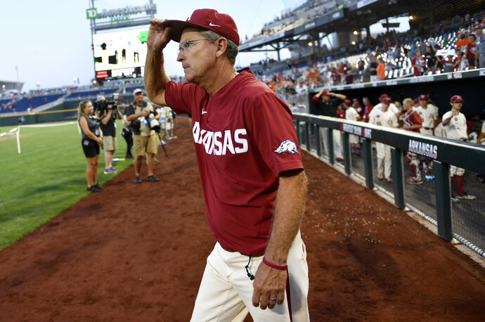 FILE - In this June 28, 2018, file photo, Arkansas coach Dave Van Horn walks from the dugout after losing to Oregon State in Game 3 of the NCAA College World Series baseball finals in Omaha, Neb. Van Horn says he's agreed to a contract extension through the 2023 season after taking the Razorbacks to a runner-up finish in last month's College World Series. Van Horn, who just completed his 16th season at Arkansas, said Tuesday night, July 10, 2018, that the deal includes options for the 2024 and 2025 season. (AP Photo/Ted Kirk File)
