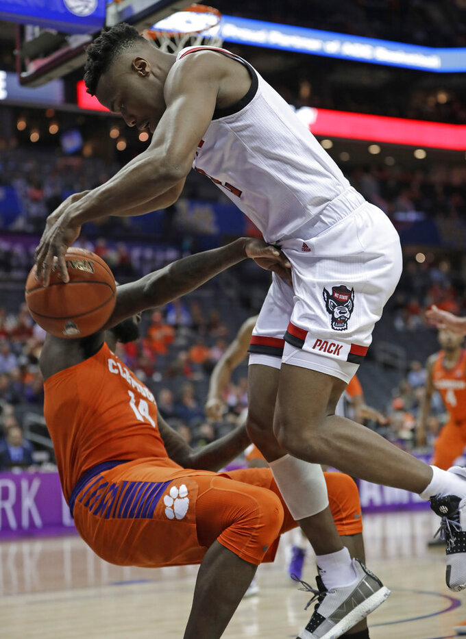 North Carolina State's Torin Dorn, right, bounces the ball of Clemson's Elijah Thomas, left, during the first half of an NCAA college basketball game in the Atlantic Coast Conference tournament in Charlotte, N.C., Wednesday, March 13, 2019. (AP Photo/Nell Redmond)
