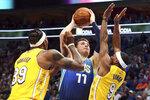 Los Angeles Lakers center Dwight Howard (39) and guard Rajon Rondo (9) defend against Dallas Mavericks forward Luka Doncic (77) during the first half of an NBA basketball game Friday, Jan. 10, 2020, in Dallas. (AP Photo/Richard W. Rodriguez)