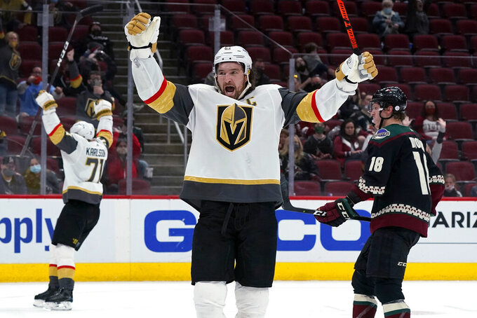 Vegas Golden Knights right wing Mark Stone, middle, and center William Karlsson (71) celebrate an overtime goal by Jonathan Marchessault, as Arizona Coyotes center Christian Dvorak (18) skates past, at an NHL hockey game Saturday, May 1, 2021, in Glendale, Ariz. The Golden Knights won 3-2. (AP Photo/Ross D. Franklin)