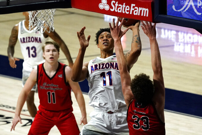 Arizona forward Ira Lee (11) shoots between Eastern Washington guard Jack Perry (11) and Jacob Groves (33) during the first half of an NCAA college basketball game, Saturday, Dec. 5, 2020, in Tucson, Ariz. (AP Photo/Rick Scuteri)