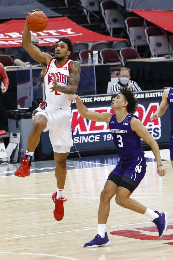 Ohio State's Musa Jallow, left, drives past Northwestern's Ty Berry during the second half of an NCAA college basketball game Wednesday, Jan. 13, 2021, in Columbus, Ohio. (AP Photo/Jay LaPrete)