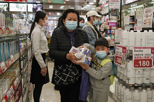 """A woman a boy purchase face masks in Hong Kong, Saturday, Feb, 1, 2020. China's death toll from a new virus has risen over 250 and a World Health Organization official says other governments need to prepare for""""domestic outbreak control"""" if the disease spreads. (AP Photo/Kin Cheung)"""