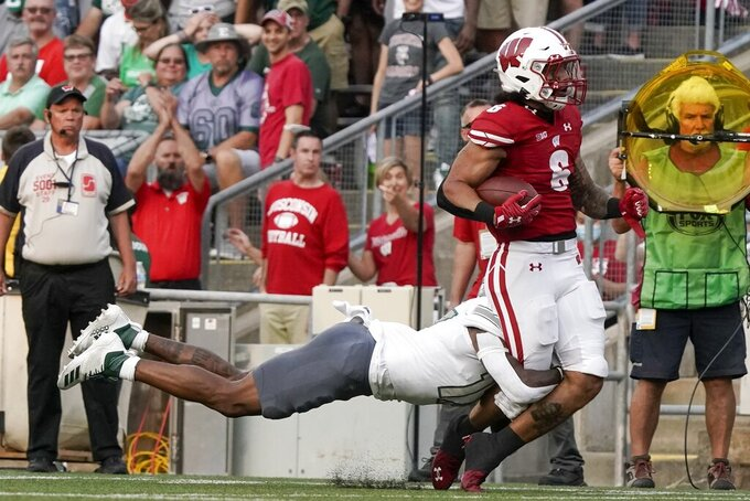 Eastern Michigan's Mark Lee Jr. stops Wisconsin's Chez Mellusi after a long run during the first half of an NCAA college football game Saturday, Sept. 11, 2021, in Madison, Wis. (AP Photo/Morry Gash)
