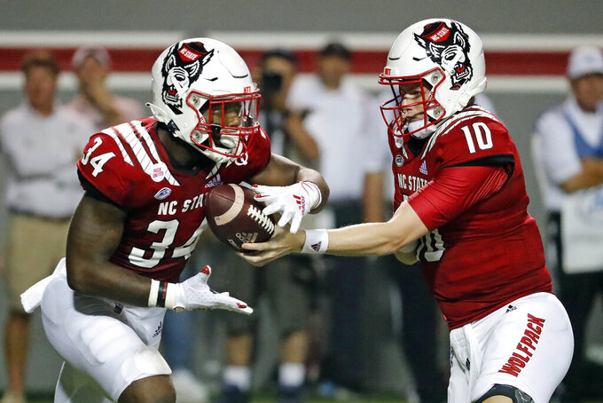 North Carolina State's Delbert Mimms III (34) takes the handoff from quarterback Ben Finley (10) during the second half of an NCAA college football game against Furman in Raleigh, N.C., Saturday, Sept. 18, 2021. (AP Photo/Karl B DeBlaker)