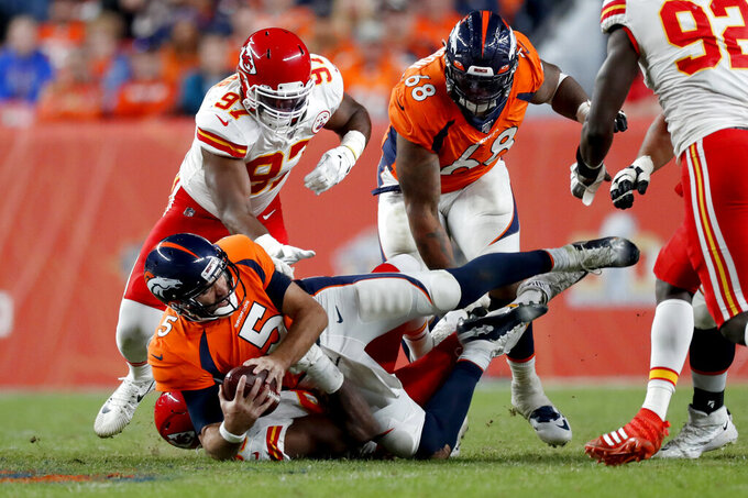 Denver Broncos quarterback Joe Flacco (5) is sacked by Kansas City Chiefs defensive end Emmanuel Ogbah (90) during the second half of an NFL football game, Thursday, Oct. 17, 2019, in Denver. (AP Photo/David Zalubowski)