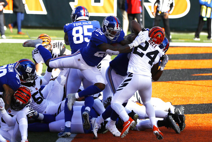 New York Giants running back Wayne Gallman (22) rushes for a 1-yard touchdown during the first half of NFL football game against the Cincinnati Bengals, Sunday, Nov. 29, 2020, in Cincinnati. (AP Photo/Aaron Doster)