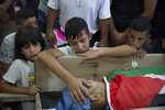 Palestinian Yousef Jadallah, places his hand on his father Raed Jadallah's body, who was killed by Israeli forces at the western entrance of his village while returning from work in the early hours of Wednesday morning, during his funeral, in the West Bank village of Beit Ur al-Tahta, Wednesday, Sep. 1, 2021. (AP Photo/Majdi Mohammed)