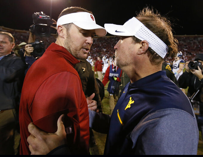 FILE - In this Nov. 25, 2017, file photo, Oklahoma head coach Lincoln Riley, left, and West Virginia head coach Dana Holgorsen, right, talk after their NCAA college football game in Norman, Okla. No. 6 Oklahoma or No. 7 West Virginia can get into the Big 12 championship game by winning their last two games. Since those Top 10 teams still have to play each other in the regular season, it is impossible for both to win their last two games. But the three-time defending Big 12 champion Sooners (9-1, 6-1 Big 12) and Mountaineers (8-1, 6-1) could also still face each other two weeks in a row _ in that day-after-Thanksgiving game in Morgantown, and then Dec. 1 for the conference title. (AP Photo/Sue Ogrocki, File)