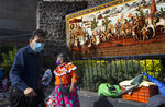 Locals walk past a mural dedicated to Spanish conquistador Hernan Cortes, in Mexico City, Monday, Sept. 28, 2020. Smallpox was an unknown disease in Mexico before the arrival of the Spanish conquistadores and exploded in the Aztec capital of Tenochtitlan after Cortes put the city under siege in 1520. Smallpox and other newly introduced diseases went on to kill tens of millions of Indigenous people in the Americas who had no resistance to the European illnesses. (AP Photo/Marco Ugarte)